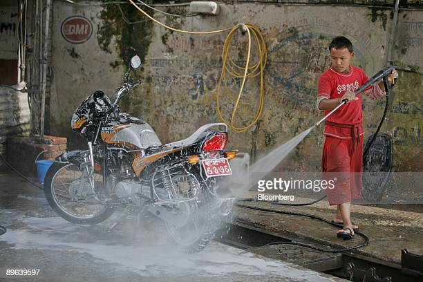 A boy washes a Hero Honda motorcycle at a gas station in Kathmandu Nepal on Wednesday June 24 2009 Nepal will step up spending on security to protect...
