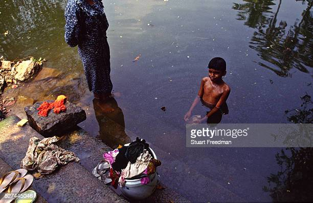 'A boy washes in the Backwaters of Ayamenam whilst his mother washes clothes The village was the setting for the Booker Prize winning novelist...