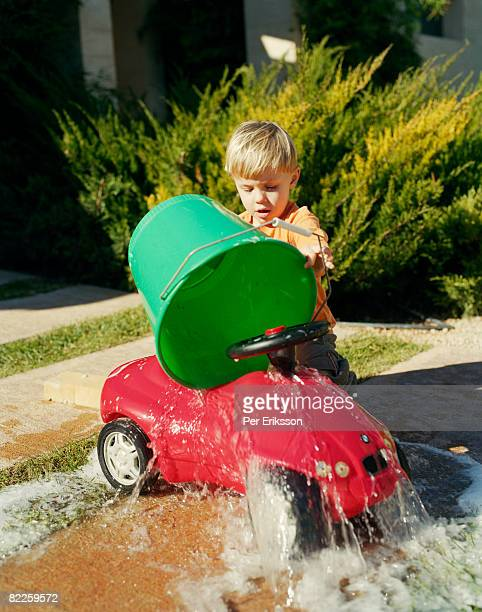 A boy washing a red car.