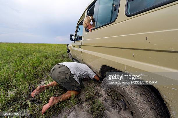 A boy watches a safari guide trying to dig out a 4wd stuck in mud