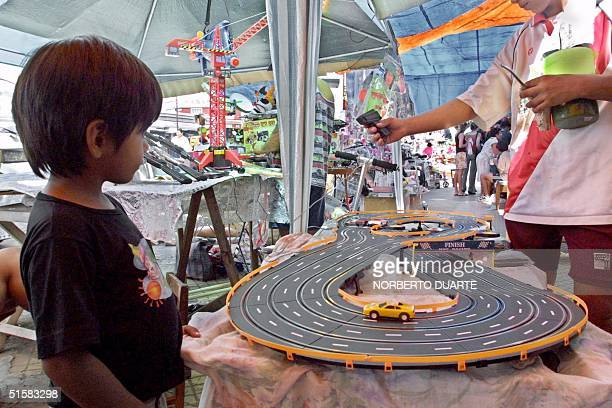 A boy watches a toy car race track at a toy store in Asuncion Paraguay 05 January 2001 the traditional day 'los Reyes Magos' eve when children...