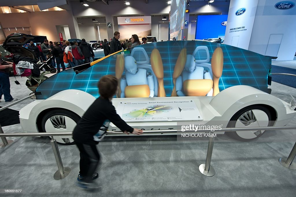 A boy watches a video of Toyota's Smart Environment Recognition future safety technology at the Washington Auto Show at the Walter E. Washington Convention Center in Washington on February 2, 2013. The show runs February 1-10. AFP PHOTO/Nicholas KAMM