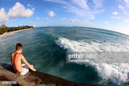Boy watches above surfers and water play in ocean : Foto de stock
