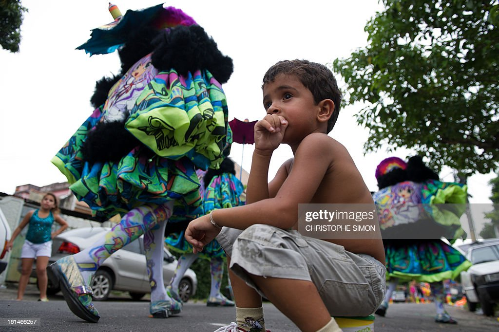 A boy watches as members of the local 'Indio' carnival group of the Guadalupe neighborhood in northern Rio de Janeiro, Brazil, take part in their 'Bate Bola' traditional parade on February 10, 2013. AFP PHOTO/Christophe Simon