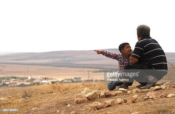 A boy watches the clashes between the armed wing of Democratic Union Party People's Protection Units and Islamic State of Iraq and the Levant with...