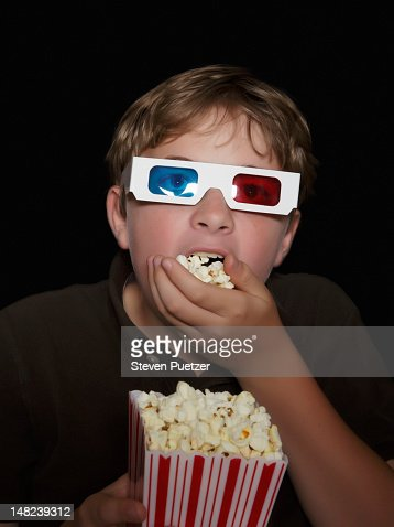 boy watching a 3d movie eating popcorn picture id148239312?s=170667a