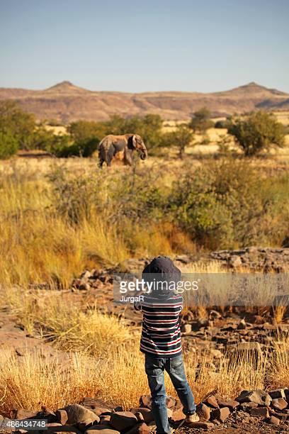Boy Watching an Elephant through binoculars on safari in Africa