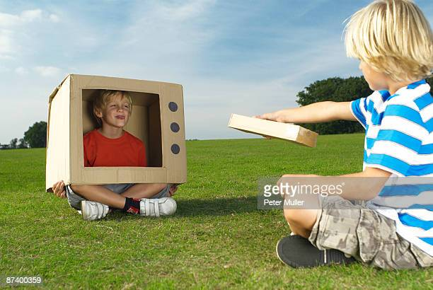 boy watching other boy in box tv