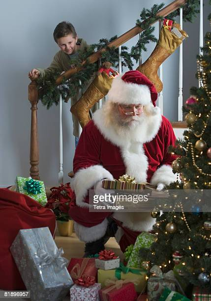 Boy watching Santa Claus leave gifts under Christmas tree