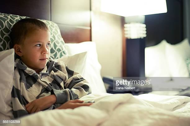 Boy watching television in bed