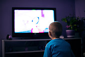 Boy watching television in dark living room