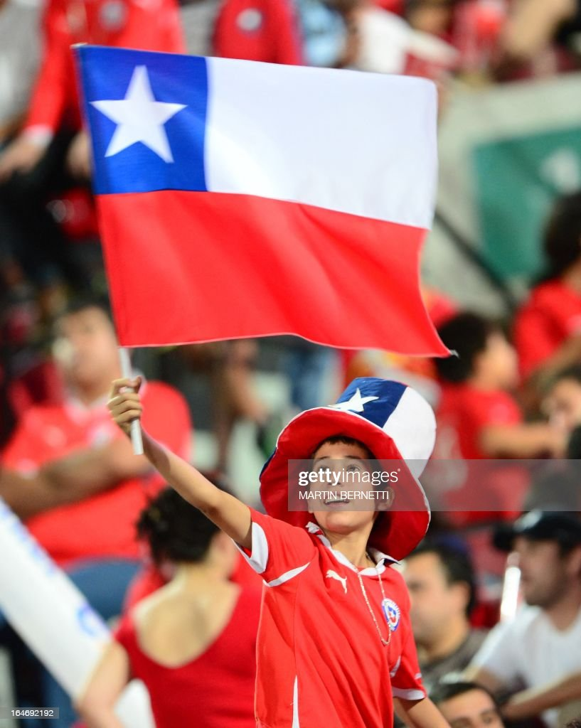A boy waves a Chilean flag before the start of the Brazil 2014 FIFA World Cup South American qualifier football match between Chile and Uruguay in Santiago, on March 26, 2013.
