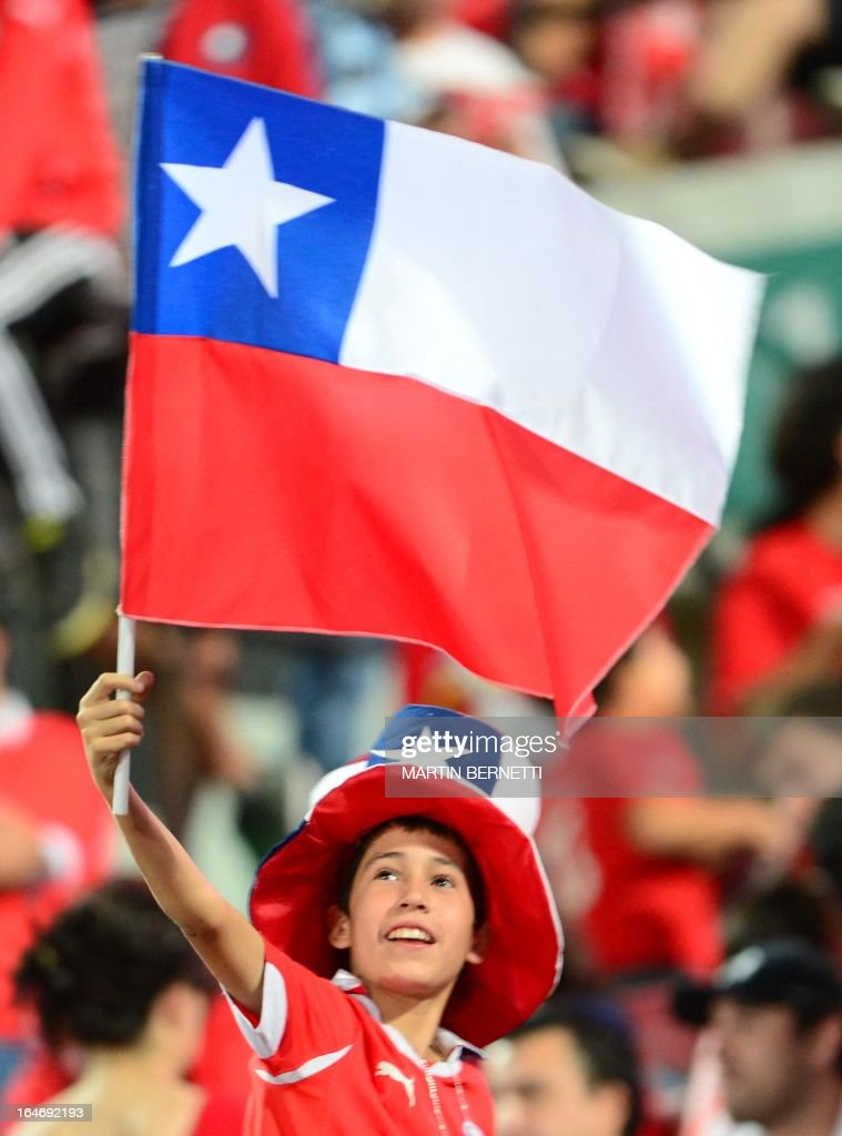 A boy waves a Chilean flag before the start of the Brazil 2014 FIFA World Cup South American qualifier football match between Chile and Uruguay in Santiago, on March 26, 2013. AFP PHOTO / MARTIN BERNETTI