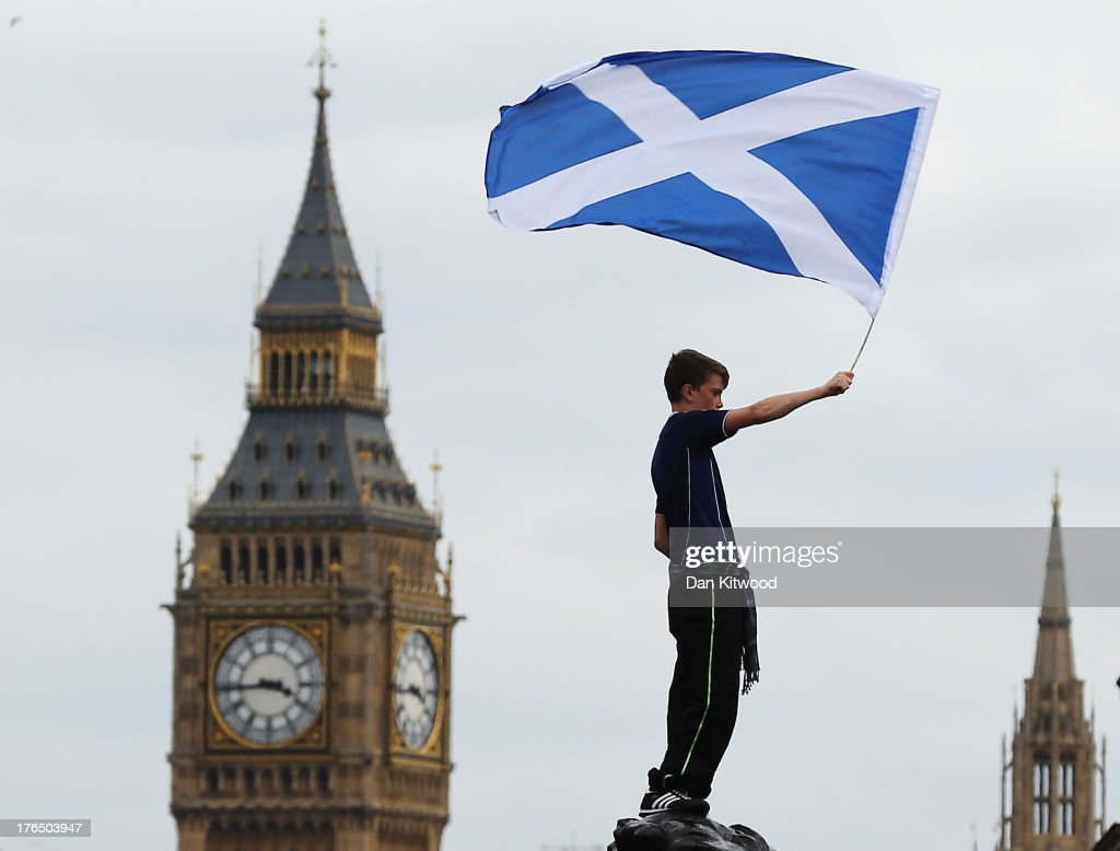 A boy waves a flag as Scotland fans gather in Trafalgar Square ahead of their friendly match against England tonight on August 14, 2013 in London, England. Scotland and England will meet at Wembley stadium tonight for their first international in 14 years.