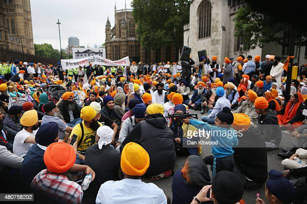 A boy waves a toy gun as Sikh protestors gather outside the Houses of Parliament on 15 July 2015 in London England Hundreds of demonstrators gathered...