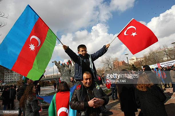 A boy waves an Azerbaijan flag and a Turkish one as he sits on the shoulder of a man attending a demonstration on February 26 2012 in Ankara to...
