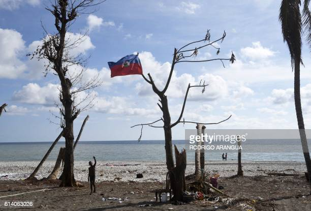 TOPSHOT A boy waves next to a national Haiti flag in a tree on a beach destroyed by Hurricane Matthew in Port Salut southwest of PortauPrince on...