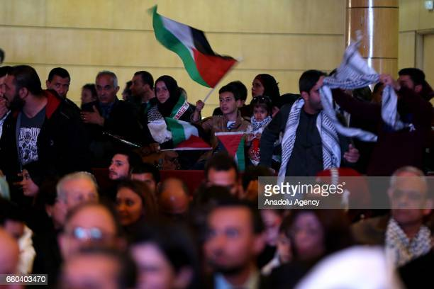 A boy waves Palestinian flag as artists perform during the 41st Palestinian Land Day at Conference Palace in Tunis Tunisia on March 30 2017