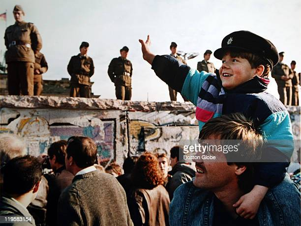 A boy waves to soldiers on the Berlin Wall in front of the Brandenburg Gate