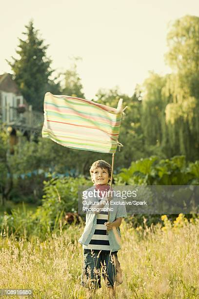 Boy waving flag in garden