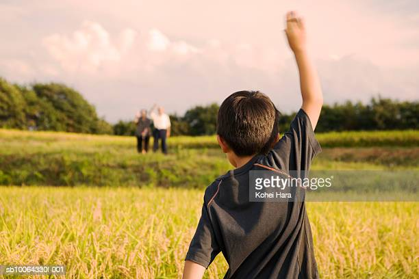 Boy (6-7) waving hand to grandmother and grandfather, rear view