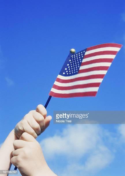 Boy (4-6) waving miniature American flag outdoors, close-up
