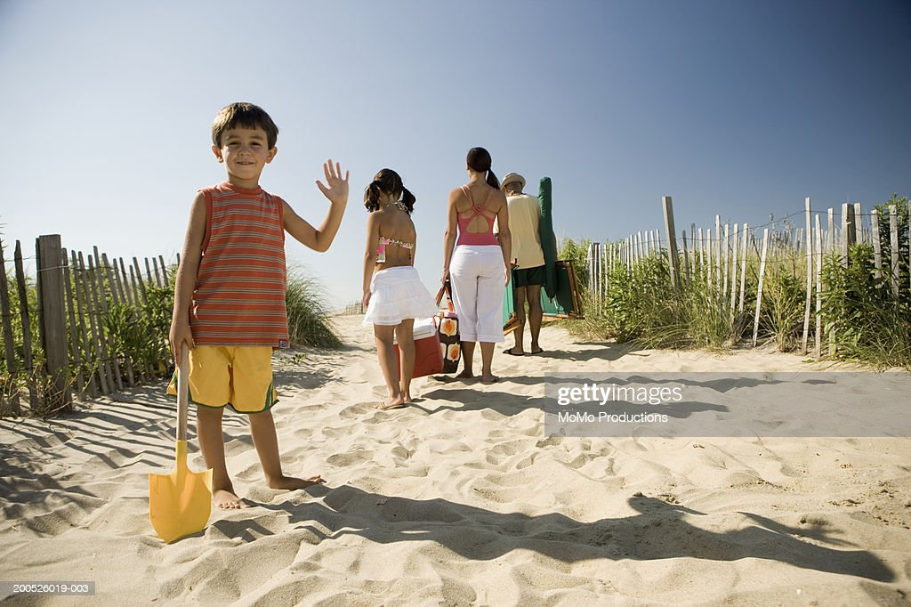 Boy (4-6) waving, parents and sister (8-10) walking towards beach : Stock Photo