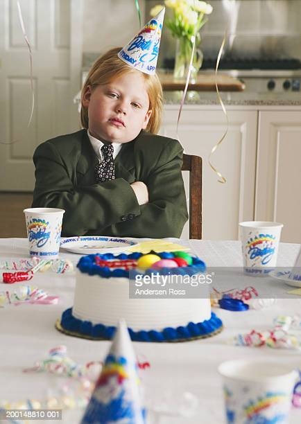 Boy (7-9) weaing suit and tie, sitting at table for birthday party