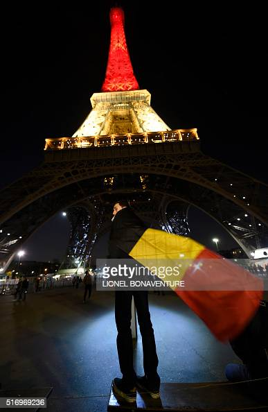 A boy wearing a Belgian flag stands under shows the Eiffel Tower in Paris illuminated in colours of the Belgian flag in tribute to the victims of...