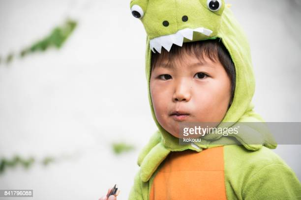 A boy wearing a dinosaur to mischief outside.