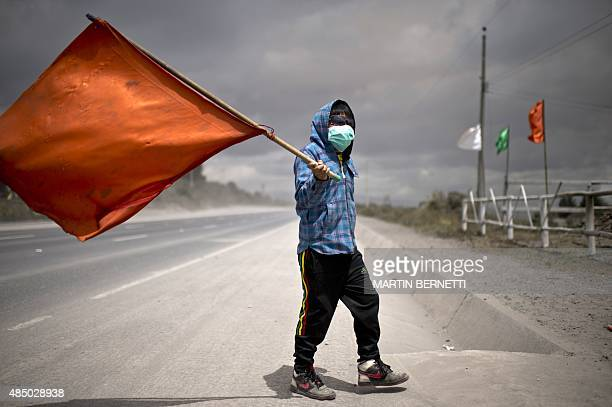 A boy wearing a face mask and holding a flag walks along a street covered with ashes of the Cotopaxi volcano in Lasso Ecuador on August 23 2015 A...