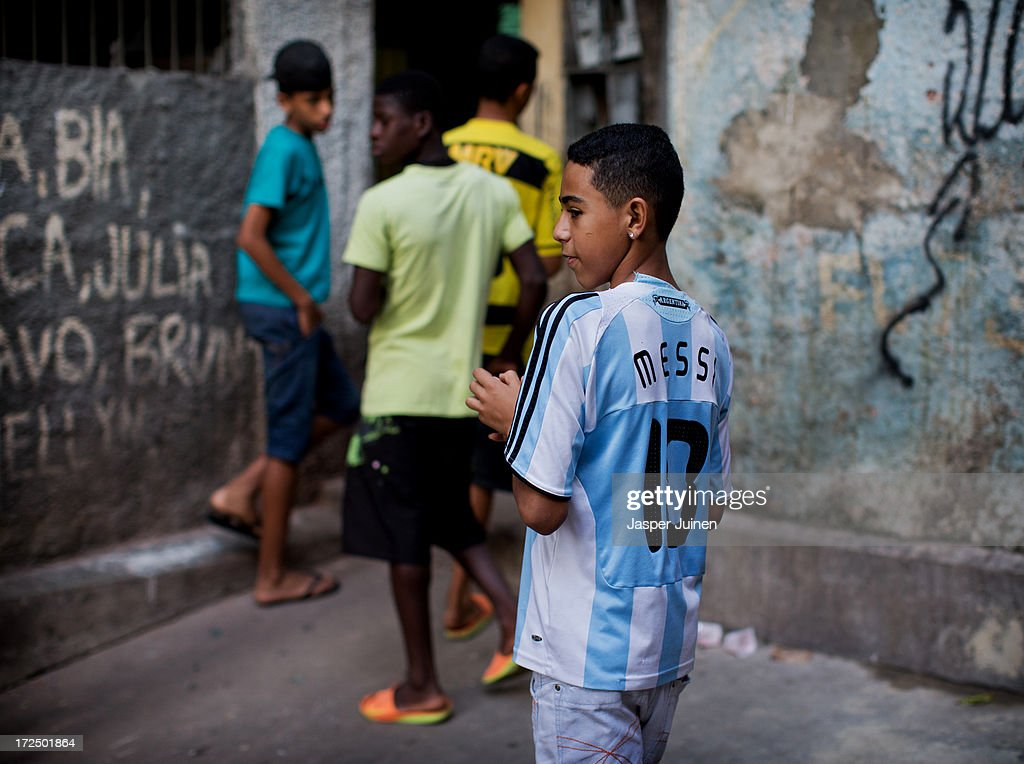 A boy wearing a football shirt of football star Lionel Messi walks with his friends through one of the many alleys of the Complexo do Alemao favela on June 29, 2013 in Rio de Janeiro, Brazil. It was at the end of 2010 that under the stage of pacification some 300 police officers went into the Complexo do Alemao with tanks and helicopters to drive out the criminal gangs to establish a permanent police presences and to set up social services such as schools, healthcare centers, and rubbish collection. The Complexo do Alemao favela is, with a population of 100, 000 and stretching for more than 3 kilometers with a maze of narrow alleys and stairways, one of the largest favelas in Rio de Janeiro.