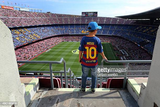 A boy wearing a jersey of Messi looks at the Camp Nou stadium before the Spanish league football match FC Barcelona vs UD Las Palmas in Barcelona on...