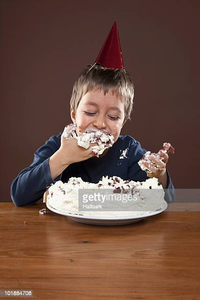 A boy wearing a party hat eating birthday cake with his hands, studio shot