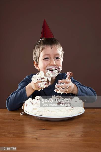 A boy wearing a party hat eating pie with his hands, studio shot