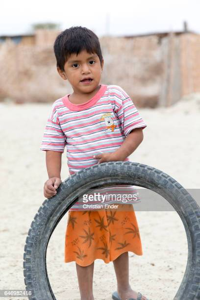 Boy wearing a pink and white striped shirt holding a rubber wheel on February 06 2015 in Piura Peru