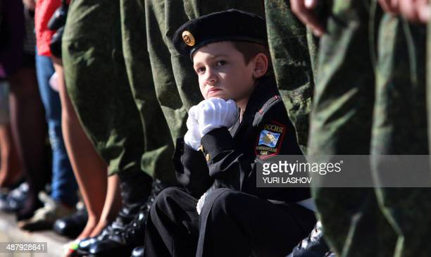 A boy wearing a Russian Navy sailor uniform watches a Victory Day parade rehearsal in Sevastpol on May 2 2014 Russia celebrates the 1945 victory over...