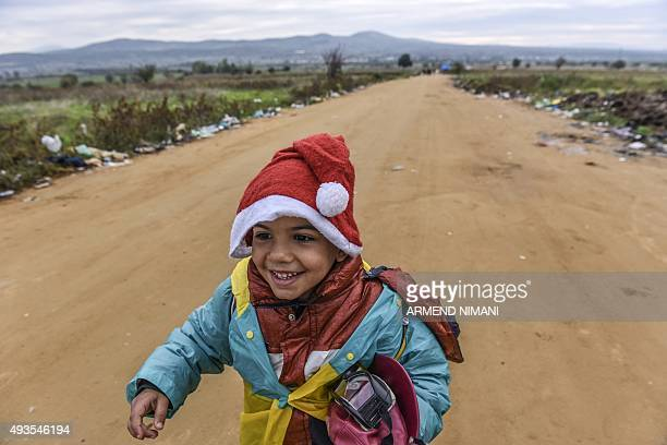 A boy wearing a Santa Claus hat walks with other migrants and asylum seekers after crossing the MacedonianSerbian border near the village of...