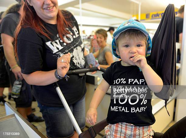 A boy wearing a tshirt reading '50 percent Papa 50 percent Mama 100 percent metal baby' at a supermarket at the Wacken Open Air heavy metal music...