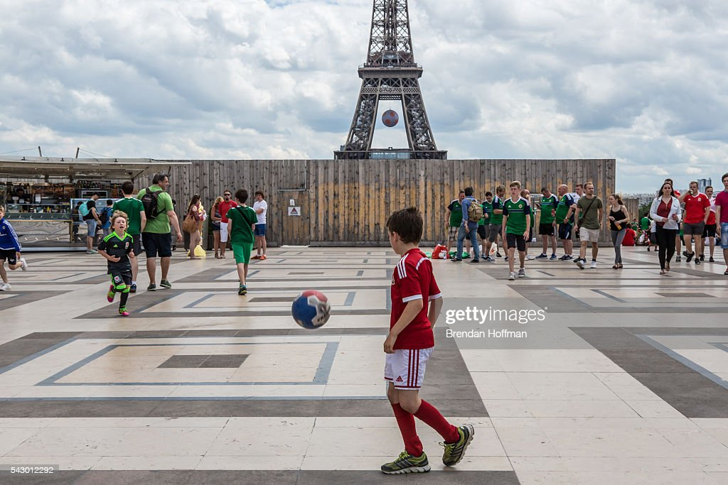 A boy wearing a Welsh team uniform plays football near the Eiffel Tower as fans prepare to watch the football match between Wales and Northern Ireland during UEFA Euro 2016 tournament on June 25, 2016 in Paris, France. Wales edged Northern Ireland in the Round of 16 at Parc des Princes in Paris.