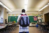 Boy wearing backpack in classroom