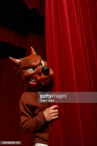 Boy (11-13) wearing bad wolf mask on stage, looking around curtain