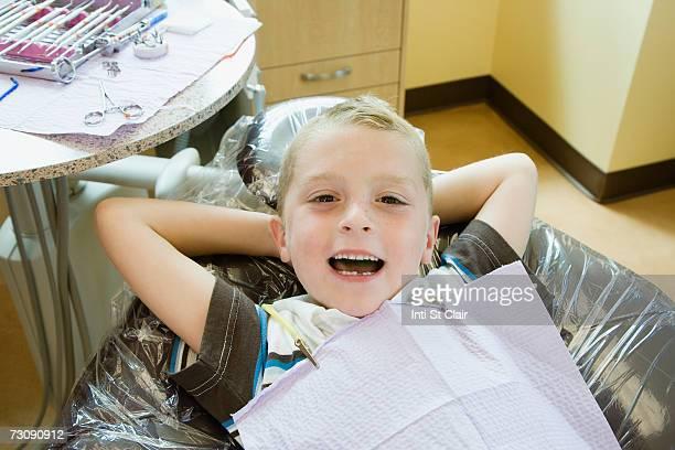 Boy (6-7) wearing bib lying in dentist's chair, smiling, portrait