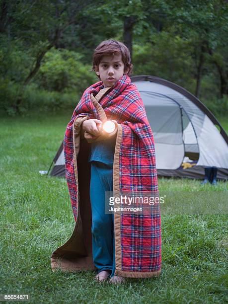 Boy wearing blanket and holding flashlight
