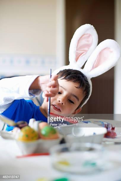 Boy wearing bunny ears painting Easter eggs