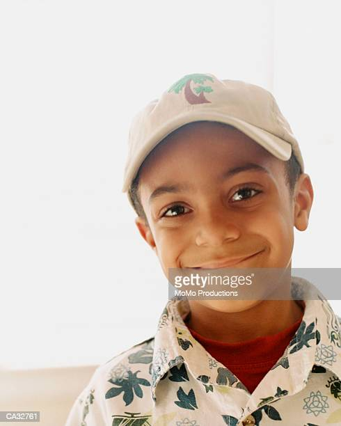 Boy (5-7) wearing cap and smiling, portrait