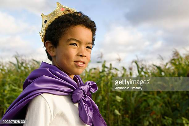 Boy (6-8) wearing cape and crown in field