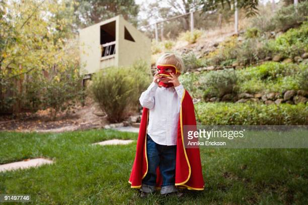 Boy wearing cape and mask in backyard