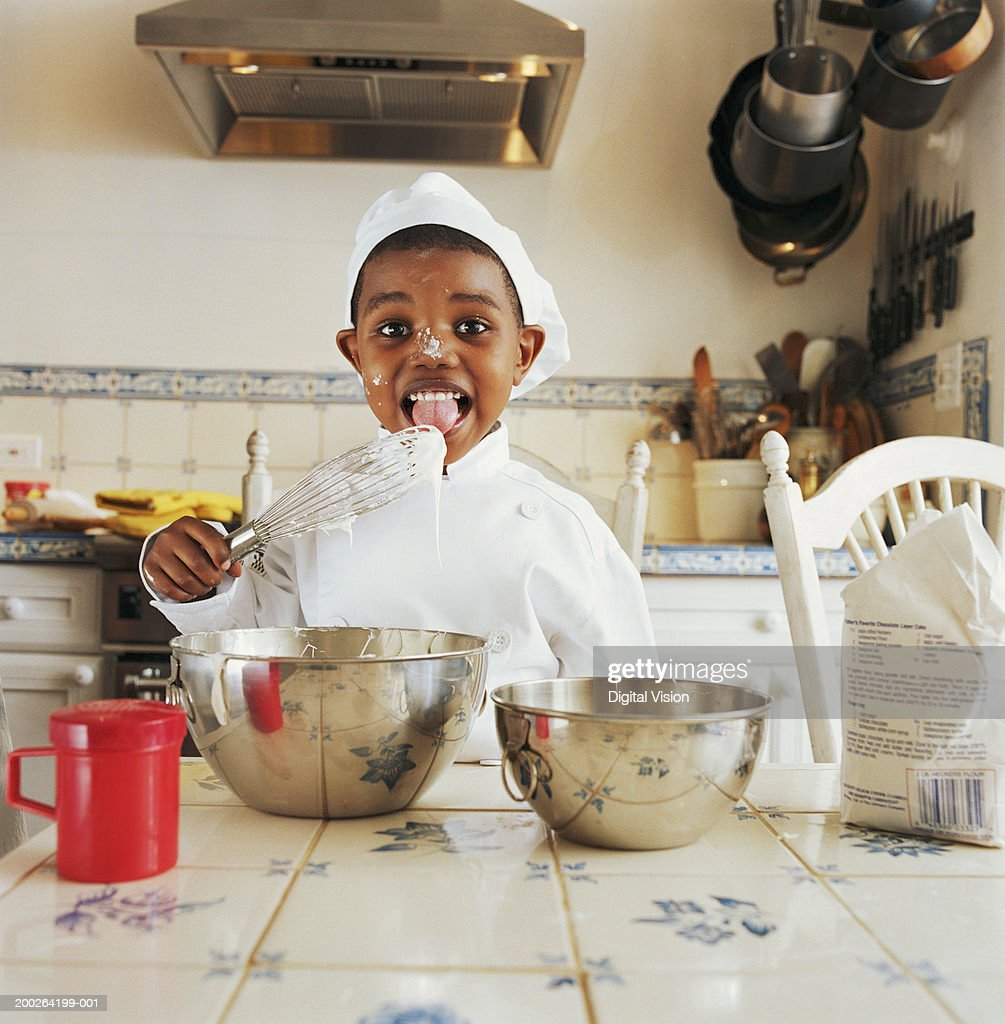 Boy (3-5) wearing chef outfit licking wisk, portrait : Stock Photo