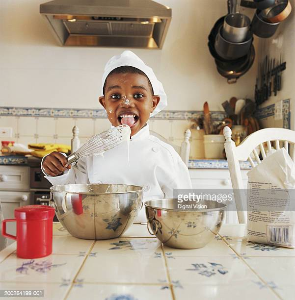 Boy (3-5) wearing chef outfit licking wisk, portrait